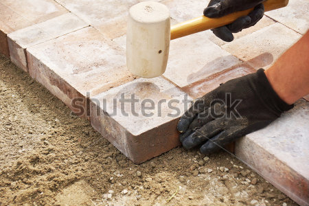 stock-photo-installing-paver-bricks-on-patio-mallet-to-level-the-stones-142053226